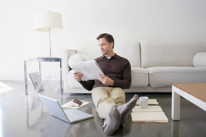 A man sitting on the floor reading a newspaper with an open laptop on one side of him and a mug on the other.