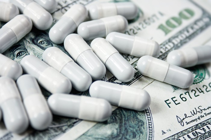 Prescription capsules lying atop hundred-dollar bills.