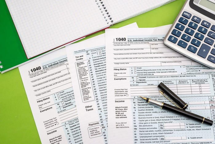 1040 tax forms with a calculator, an open graph notebook, and black fountain pen on a green background.