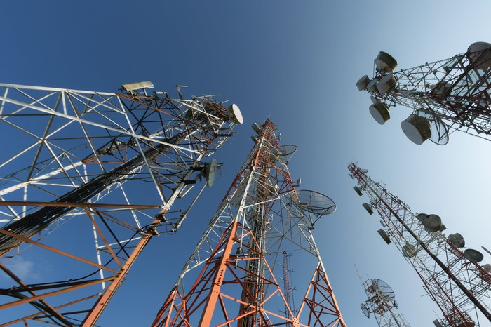A view from the ground looking up at five telecom towers.