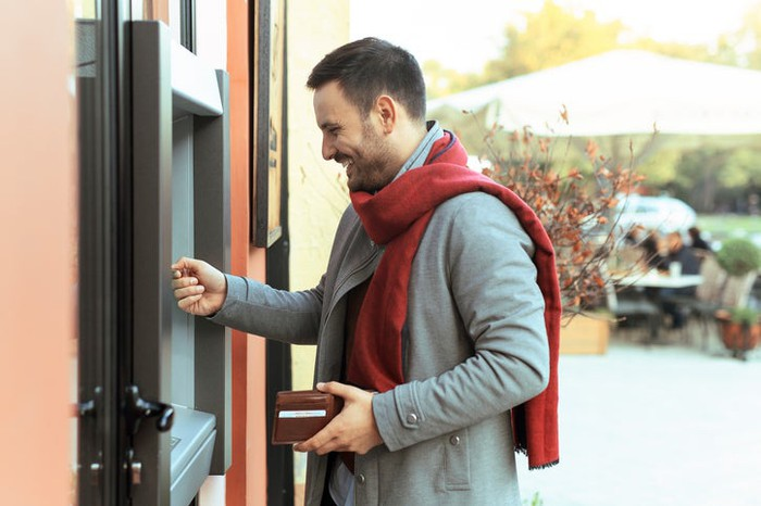 A person in a coat and red scarf smiling while using an ATM.