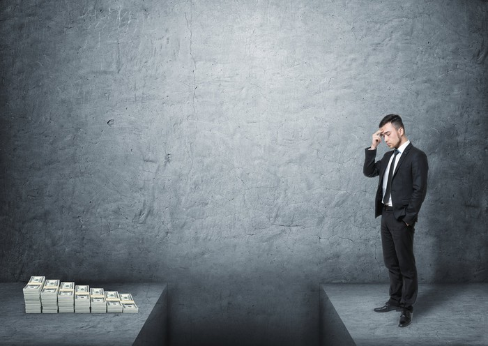 A frustrated man wearing a suit standing in front of a pile of money with a deep gap in the ground dividing them