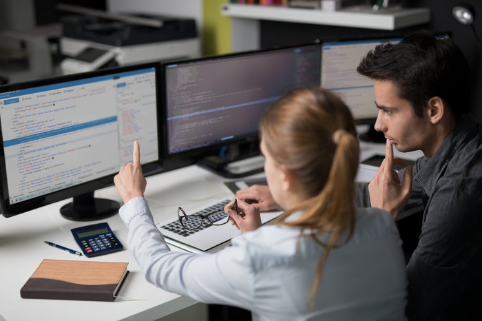 Software engineers working together in front of three computer displays