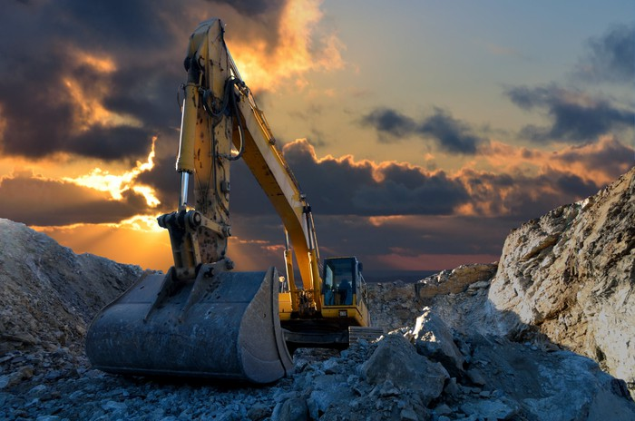 An excavator in a stone quarry at sunset.