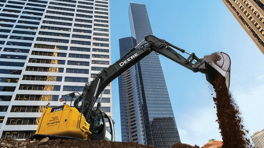 A John Deere equipment on a high-rise construction site.