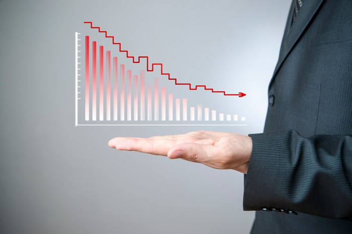 A man in a business suit holding his hand out while a stock chart showing losses hovers over it.