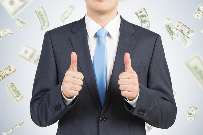 A person in a suit giving thumbs up as money falls in the background.