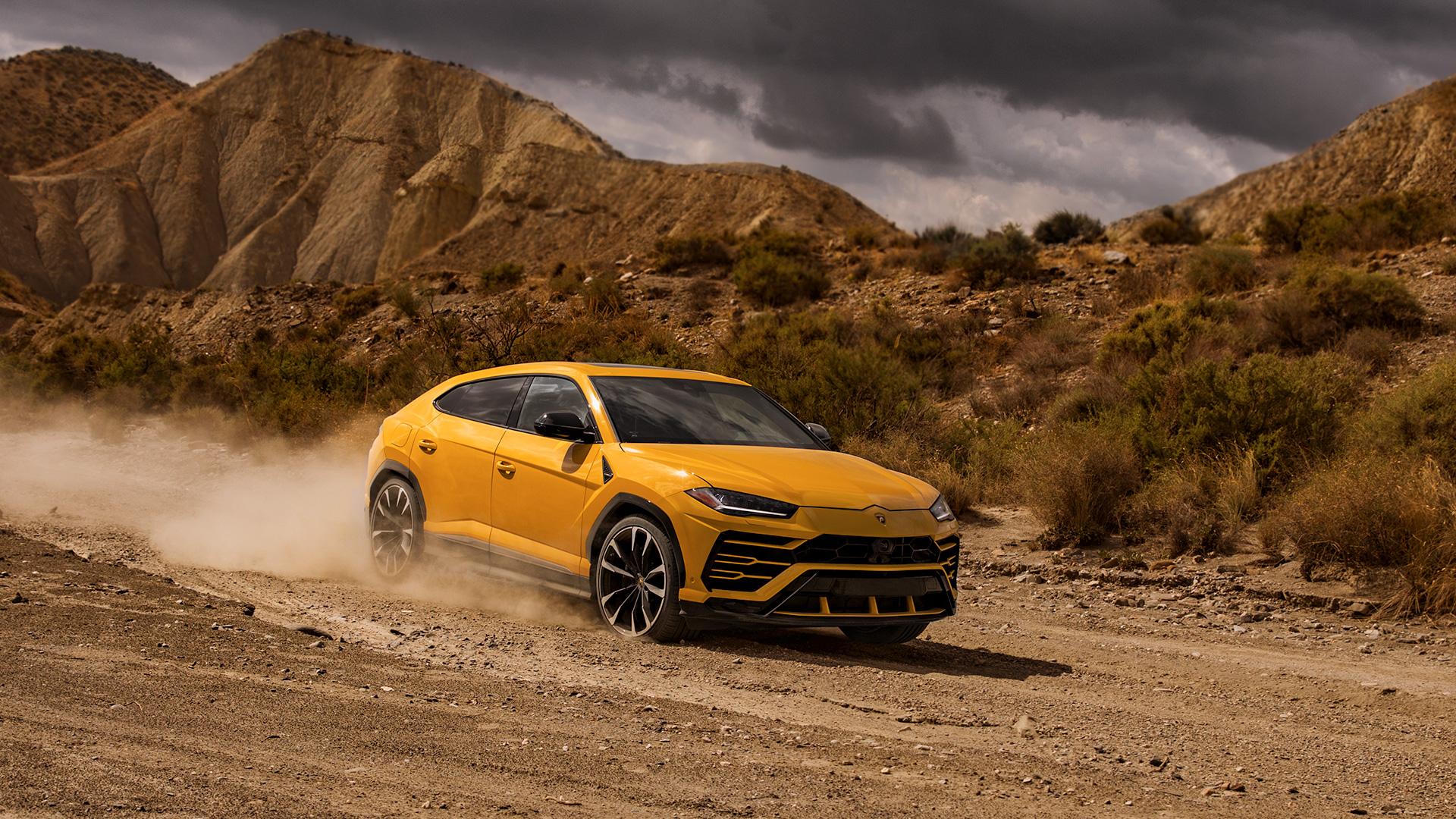 A yellow Lamborghini Urus driving offroad in a desert.