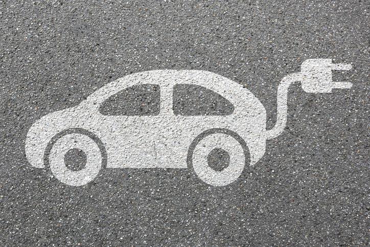 An electric car drawn in chalk on the sidewalk.
