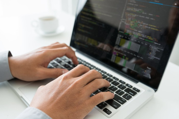 A person writing a blockchain app in code on their laptop.