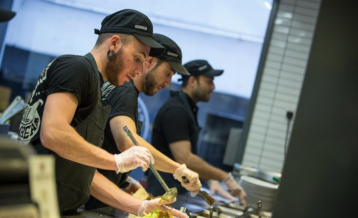 Chipotle workers assemble food.