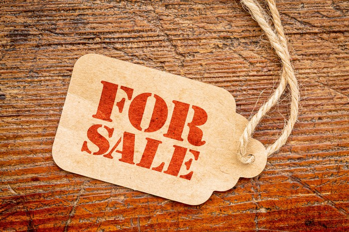 """A clothing tag labeled """"for sale"""" on a wooden table"""