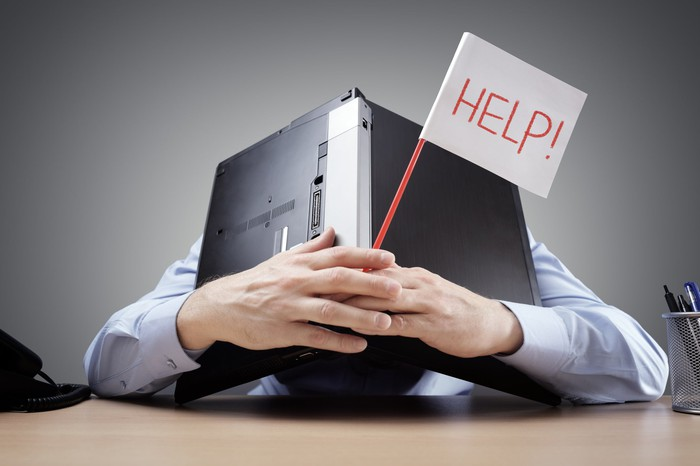 A person holds a flag that says help while hiding under a laptop.