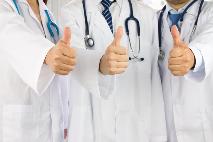Three medical professionals in white coats giving the thumbs up.