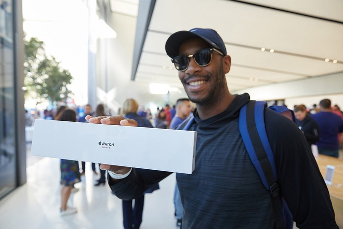 An excited customer holds an Apple Watch 3 Series in a box at an Apple Store.