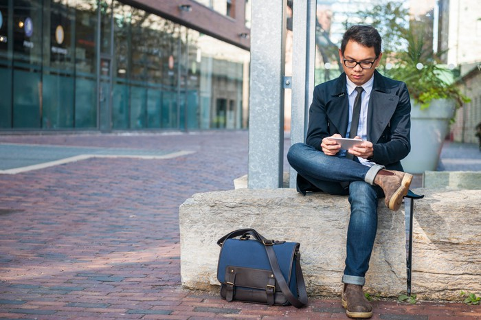 A bespectacled man in jeans and a suit jacket with his blue messenger bag on the ground as he checks his mobile phone while seated on a concrete bench outdoors