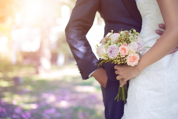 A couple in wedding outfits embraces while the woman carries a bouquet.