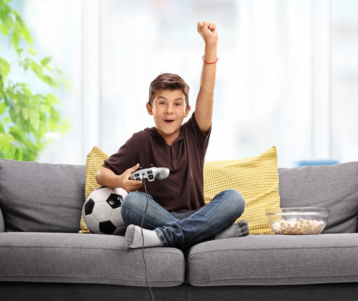 A boy sitting on a couch next to a soccer ball and a bowl of popcorn, and holding a video game controller, smiling with his arm reaching up into the air.