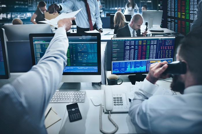 Stock trading room, with traders on the phone and sitting in front of monitors.