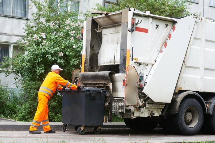 Garbage worker and bin outside a garbage truck