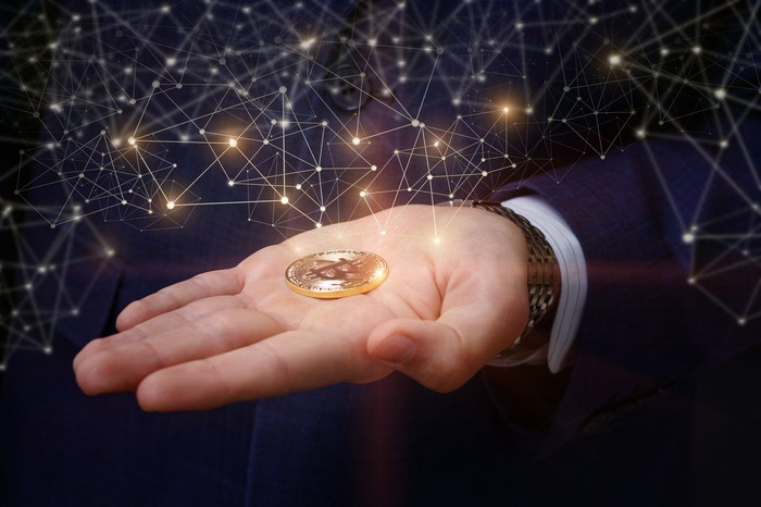 Person holding a gold coin with bitcoin symbol in open palm.