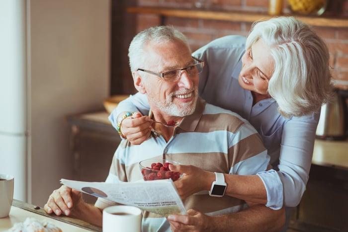 Loving aged couple enjoying their breakfast.