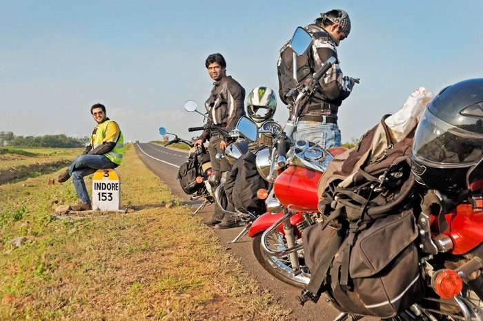 Indian motorcyclists stopped on side of road.