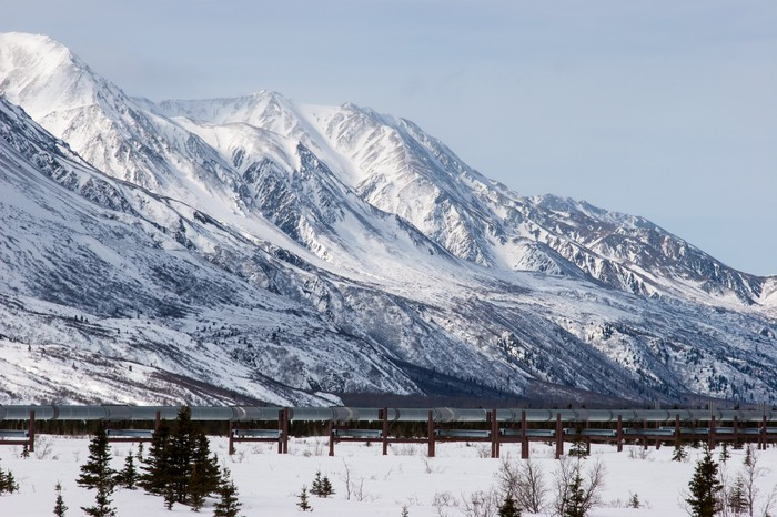 A pipeline near snow covered mountain.