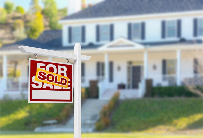 """A house has a """"sold"""" sign in front of it."""