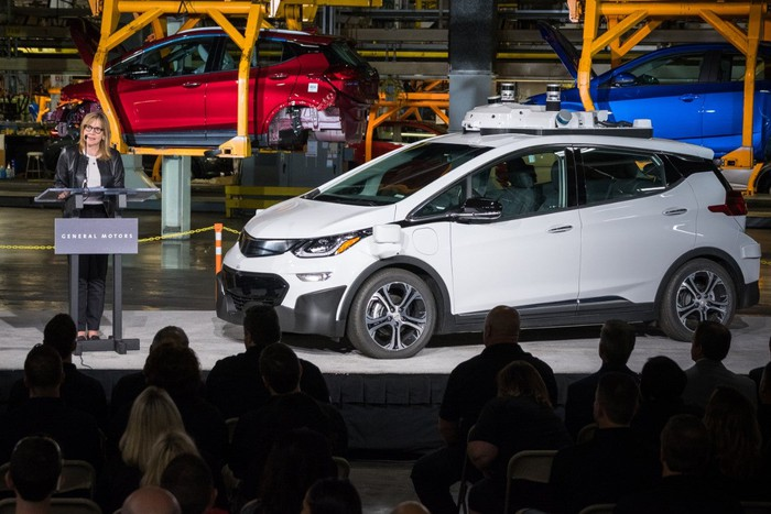 A self-driving Chevy Bolt  sits on a factory floor.