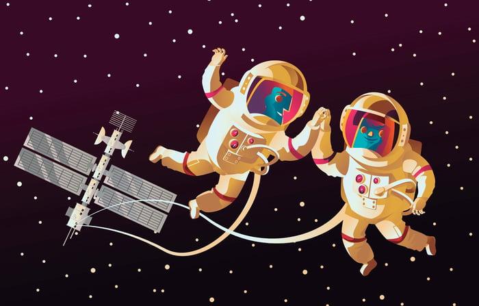 Cartoon astronauts on a space walk near ISS