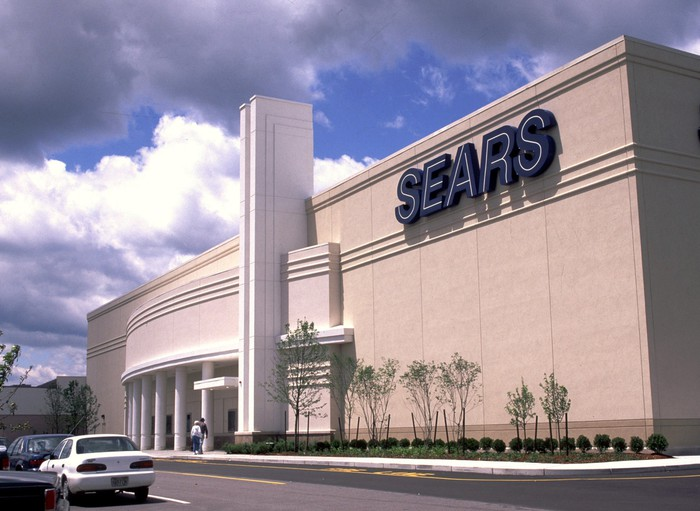 The exterior of a Sears full-line department store during the day with two customers about to walk in and cars driving in front of it