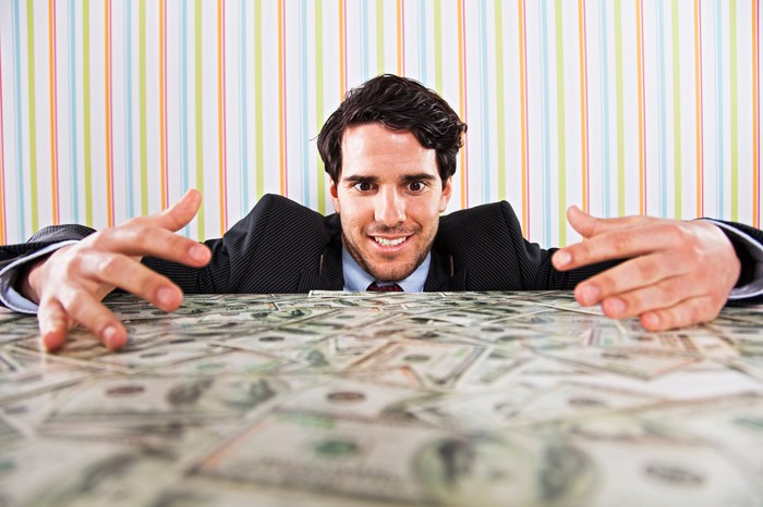 A smiling businessman, eyes wide open, admiring a messy pile of cash on a table with his arms around the dollar bills as if trying to embrace them.