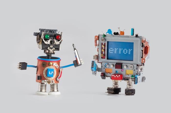 A robot tries to repair a broken robot.