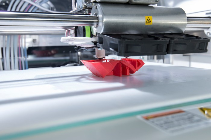 An industrial 3D printer printing an unidentifiable red plastic object.