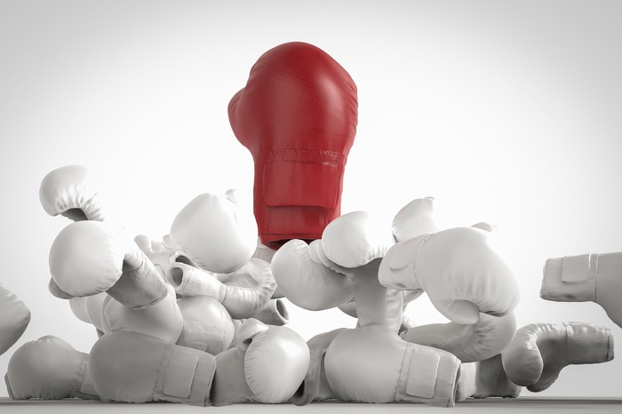 A red boxing glove bursts out through a pile of smaller white boxing gloves.