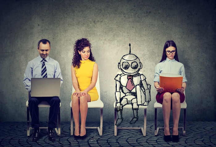 A robot sits with three human workers.