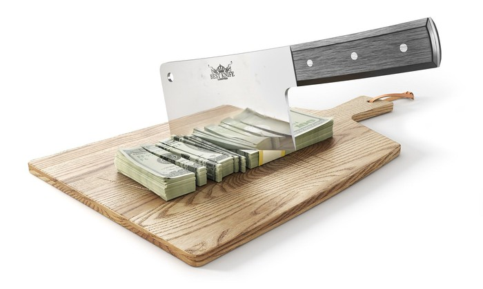 A cleaver cutting through a stack of money on a chopping board.