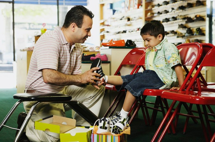 A man helps a young boy try on a pair of shoes in a shoe store.