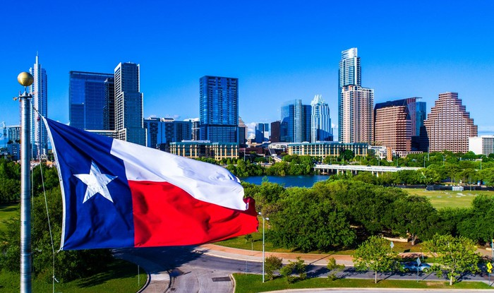 Texas flag flying in front of Austin skyline.