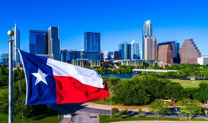 Texas flag flying in front of Austin skyline.