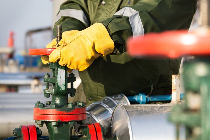 A worker in a coat and yellow work gloves turning a valve.