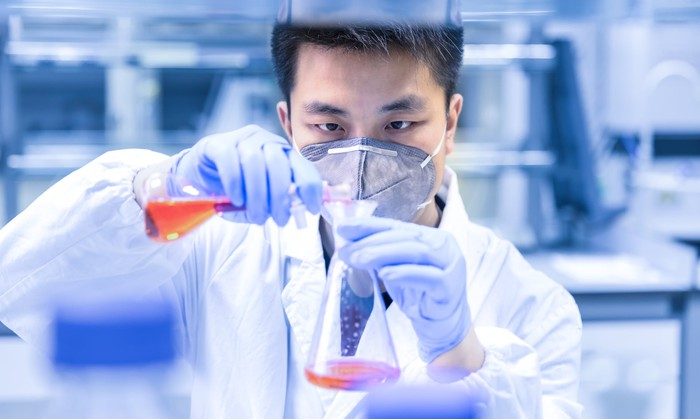 Scientist wearing white coat, face mask, and purple gloves pouring orange liquid from one flask to another in a lab