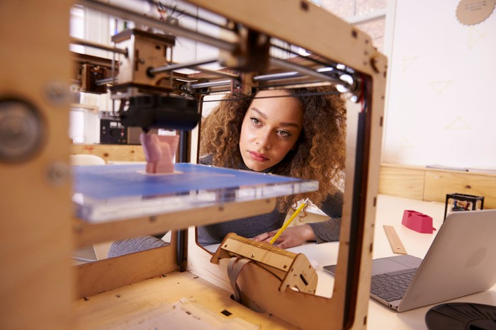 Woman looking at 3D printer.