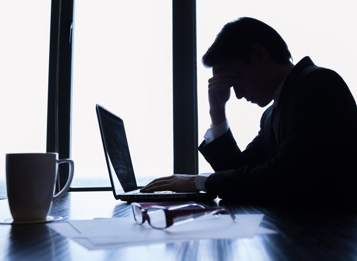 A person in a suit looking worried in front of their laptop.