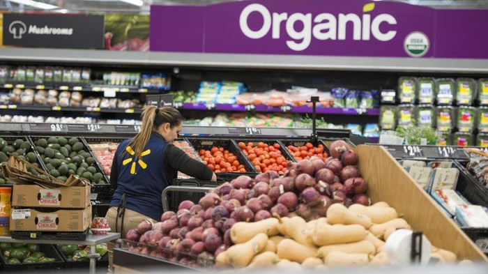 A Walmart employee stocks items in the produce section.