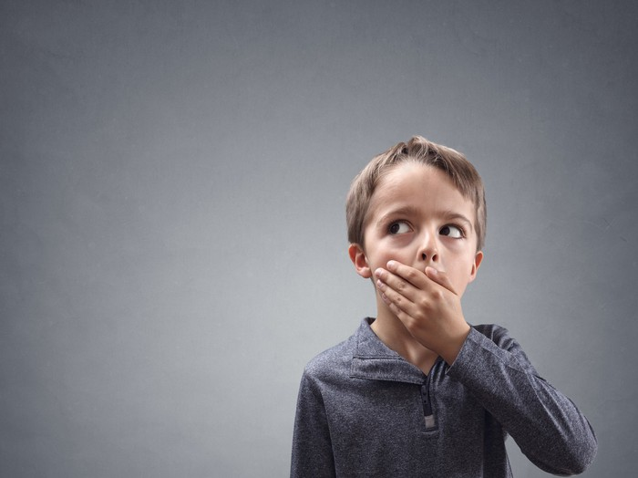 """Blond child with grey shirt covering mouth, clearly thinking """"oops"""""""