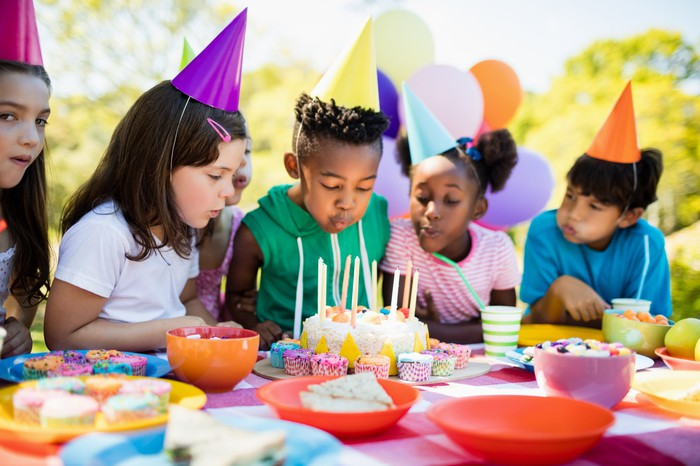 Children watching a boy blow out birthday candles