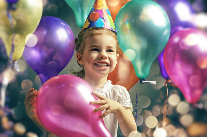 Young girl holding a pink balloon while surrounded by balloons in other colors