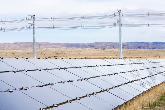 Solar array in front of power lines in a field.